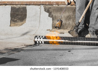 Roll roofing Installation with propane blowtorch during construction works