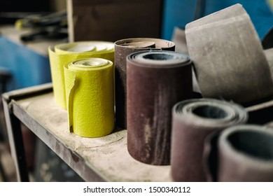 Roll of sandpaper of different color and size on workspace.