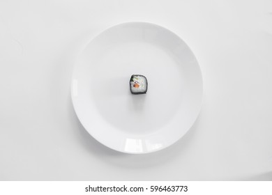 Roll of sushi on a plate, Sushi roll on a tablet, white background, Sushi roll and hand with chopsticks. Japanese food