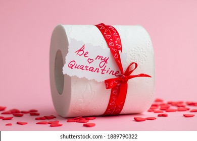 Roll of toilet paper as Valentine's Day gift with note Be My Quarantine, next to red hearts on pink background