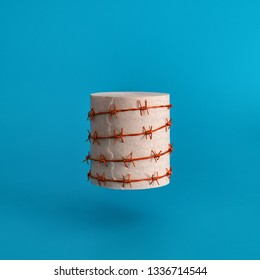 A roll of toilet paper wrapped in red barbed wire on a blue uniform background. Strange funny joke.