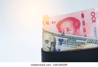 Roll of US dollar and Yuan banknote in black wallet on white background. United States and China have vat and tariff trade war to barrier goods together. Business concept.