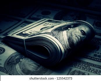 Roll of US dollars in dark style. Blue tone.