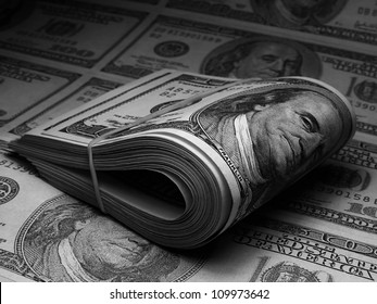 Roll of US dollars on a letter with printed dollars