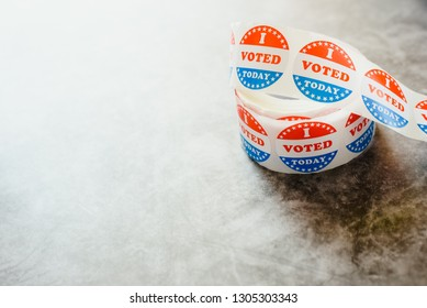 Roll of I voted circular stickers on a gray background for the November elections in the United States.