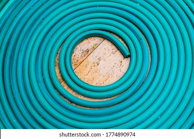 Roll of water hose on concrete floor, Thailand.