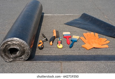 Roll waterproofing, brush, wire brush, trowel, knife gloves. Tool for waterproofing on a background of flat roof. flat roof.