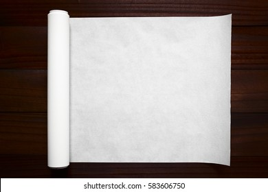 Roll of white baking paper photographed overhead on dark wood with natural light