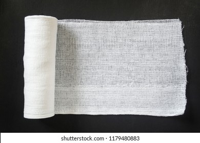 A roll of white medical bandage on a black background.