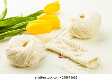 roll of white soft knitting yarn, knitting mittens and yellow tulips on lighten background