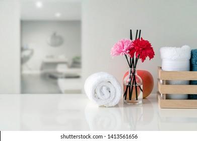 Aufrollen weißer Handtücher auf weißem Tisch mit Kopienraum auf unscharfem Wohnzimmerhintergrund. Für Produktdarstellung-Montage.