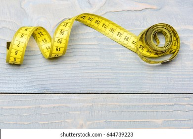 Roll of yellow measuring tape on vintage wooden background with copy space as symbol of tailoring, sewing and accuracy, top view