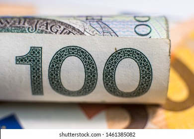 Roll of zloty banknotes (PLN) lying on euro banknotes. Perfect for topics that determine the relationship between the Euro currency and Polish Zloty