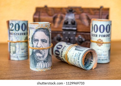 Rolled up 20000 forint banknotes with a closed vintage wooden box in the background