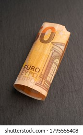 rolled up 50 euro banknote on a dark background.