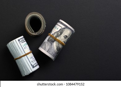 Rolled american dollars on black background top view