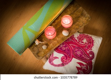 Rolled up aqua or teal yoga mat with pattern. Detail of yoga pad for studio or home practice. Still life of meditation accessories for relaxation or peace of mind. Zen candles, pillows and blanket,