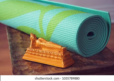 Rolled up aqua or teal yoga mat on rustic wooden stool with reclining buddha figurine. Travel to Thai meditation retreat.