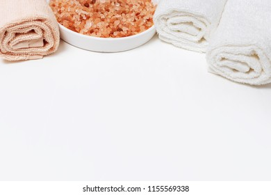 Rolled bath towels and aromatic sea salt for bath. Spa theme. Spa still life. Copy space.