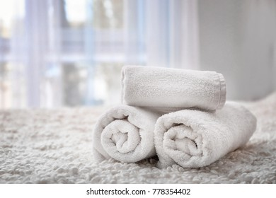 Rolled bath towels on bed in hotel suite