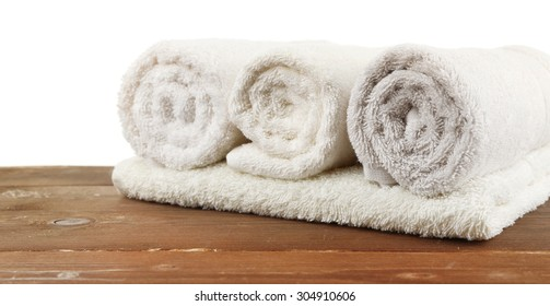 Rolled bath towels on wooden table, closeup