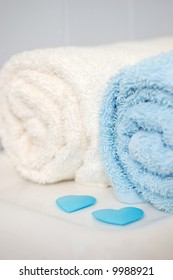 Rolled bathroom towels, sitting on toilet with blue scattered hearts