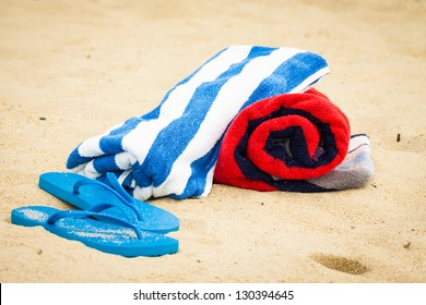 Rolled up beach towels and sandals or flip flops on a beach.