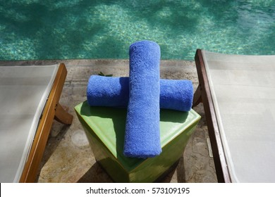 Rolled blue towel by the pool