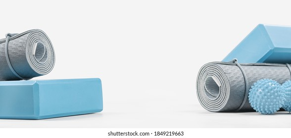 Rolled blue yoga mat and foam block or brick, massage ball. Gender neutral fitness and exercise concept accessories with copy space. Active lifestyle. Workout at home or gym, sports club banner
