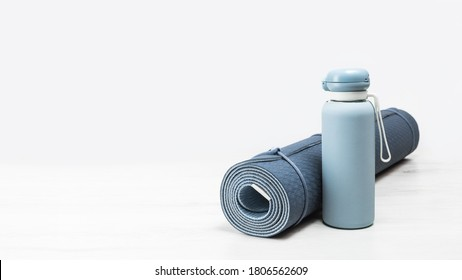Rolled blue yoga mat and blue water bottle on grey wooden surface. Gender neutral fitness yoga and exercise concept with copy space. Active lifestyle. Workout at home or gym banner