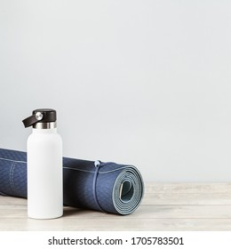 Rolled blue yoga mat and white metal water bottle flask on grey wooden surface. Gender neutral fitness and exercise concept and hydration with copy space