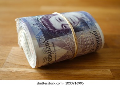 A rolled up bunch of bank notes, giving the impression of wealth.