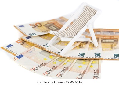 Rolled Up Bundle Of Fifty euro Banknotes bills, On Miniature Deck Chair sun lounger. Concpet of prices, costs of holiday, travel.