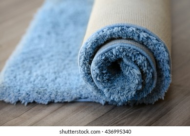 rolled up carpet lying on the parquet floor