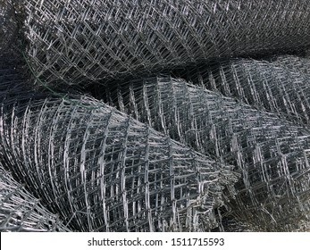 Rolled chain-link fence. Metal mesh netting rolled into rolls.