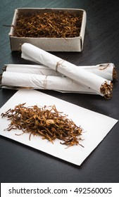 Rolled cigarettes tobacco on black table