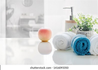 Rolled of clean towels on white table with blur background of living room, copy space for product display.