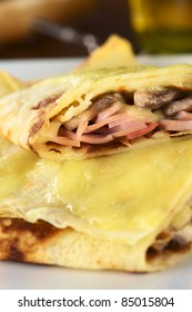 Rolled crepes filled with ham, cheese and white mushroom and baked with grated cheese on top (Selective Focus, Focus on the filling of the upper half crepe)