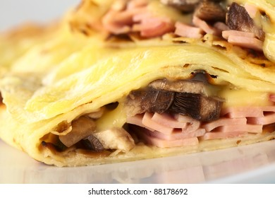 Rolled crepes filled with ham, cheese and white mushroom and baked with grated cheese on top (Selective Focus, Focus on the mushroom pieces of the lower half crepe)
