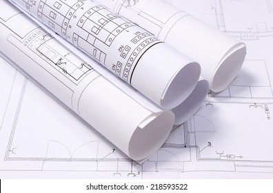 Rolled electrical diagrams lying on construction drawing of house, drawings for the projects engineer jobs