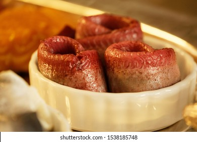 Rolled fillet of red wine dipped herring in round dish