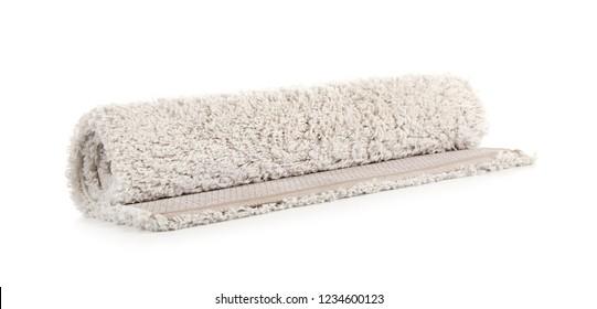 Rolled fuzzy carpet on white background. Interior element