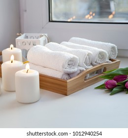 Rolled hand towels on a tray next to the lighted candles and a bouquet of tulips in the spa salon