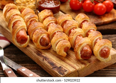 Rolled hot dog sausages baked in puff pastry on wooden background