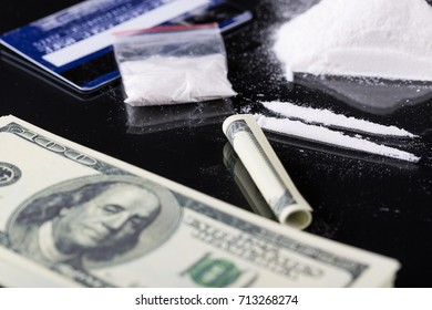 Rolled hundred dollars banknote, two lines and plastic packet of cocaine on black background, closeup.