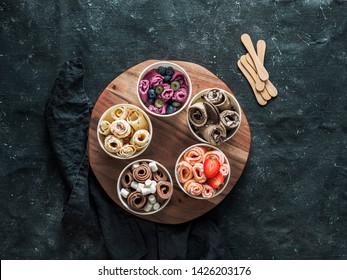 Eis in Kegelbechern auf rustikalem, rundem Holzträger auf dunklem Hintergrund gewickelt. Verschiedene vereiste Rollen Draufsicht oder flache Lage. thailändisches Walzeis