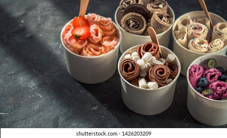 Rolled ice cream in cone cups on dark background. Different iced rolls or Thai style rolled ice cream with copy space for text or design. Banner. Natural hard daylight