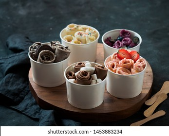 Rolled ice cream in cone cups on rustic round wooden tray over dark background. Different iced rolls or thai style rolled ice cream