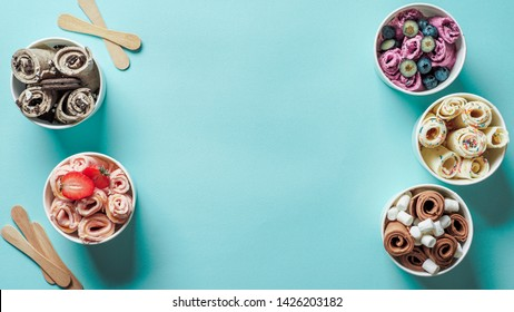 rolled ice creams in cone cups on blue background. Different iced rolls top view or flat lay. Thai style rolled ice cream with copy space in center for text or design. Banner