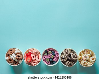 rolled ice creams in cone cups on blue background. Different iced rolls top view or flat lay. Thai style rolled ice cream with copy space for text or design